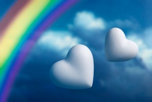 Two hearts and rainbow against a blue sky