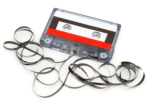 A cassette tape has been destroyed and the tape unraveled.