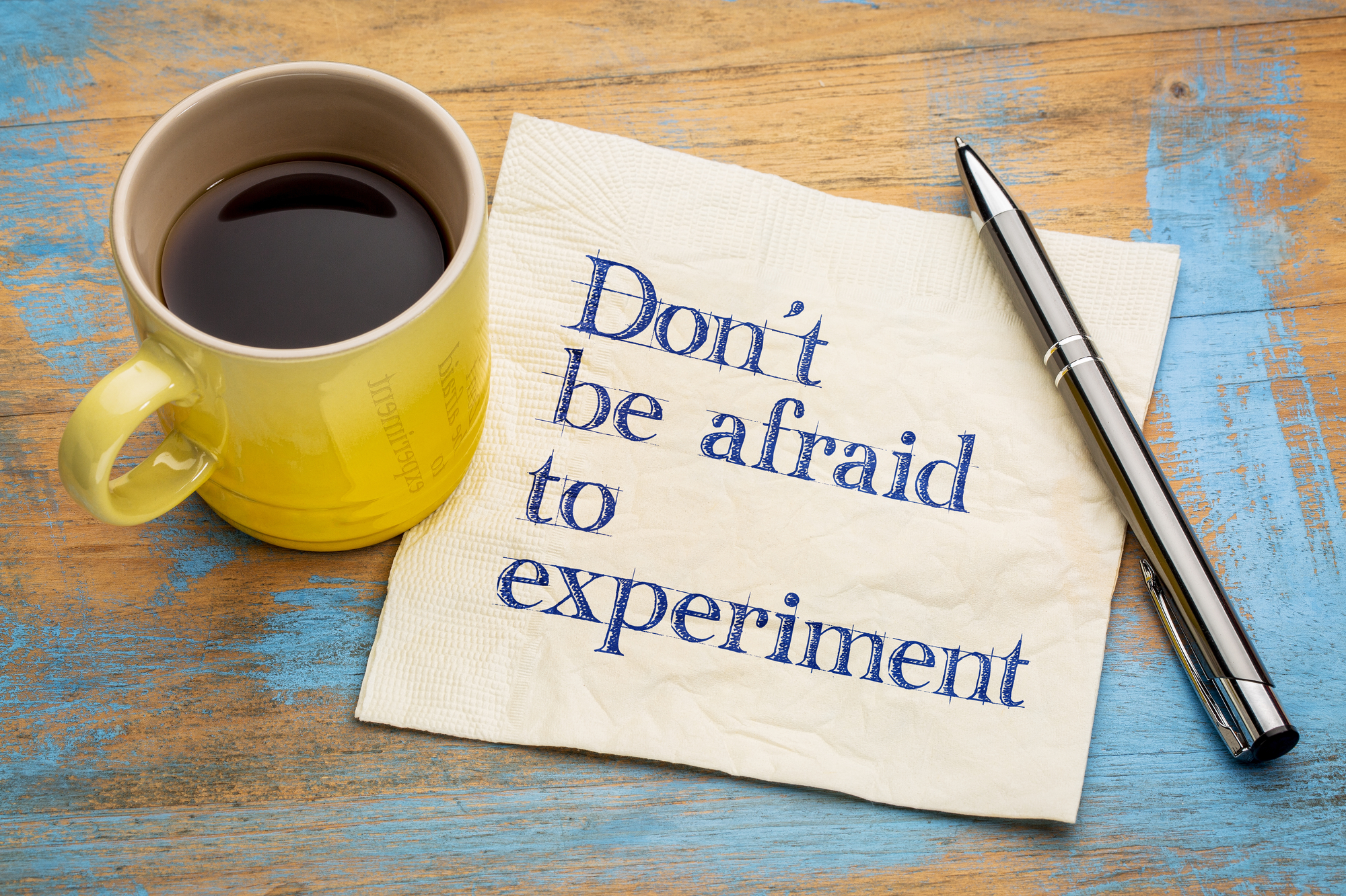 Do not be afraid to experiment - handwriting on a napkin with a cup of espresso coffee